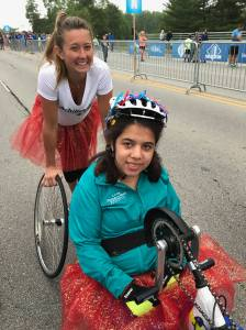 Guide Amanda Hachey behind Athlete Sara Solomon in handcycle at Geist Half Marathon